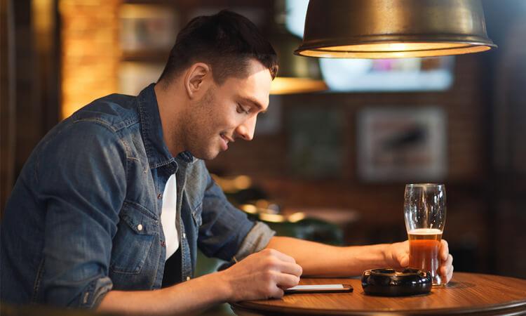 Mann in Bar surft mit Smartphone
