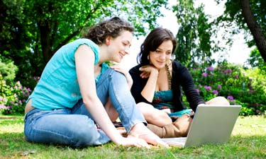 Zwei Frauen sitzen mit Laptop im Park
