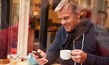 Mann mit Smartphone im Café
