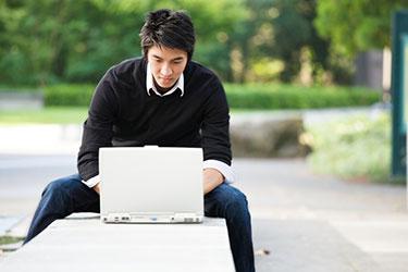 Mann mit Laptop im Freien