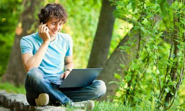 Mann mit Laptop und Handy